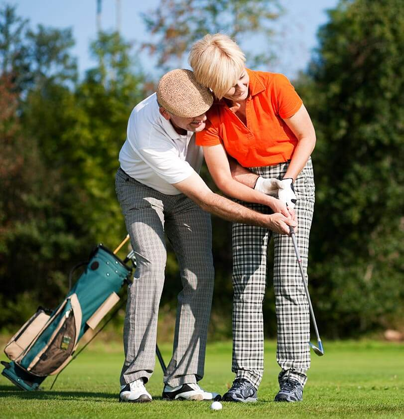 Man and woman playing golf. Man helping woman with her swing.