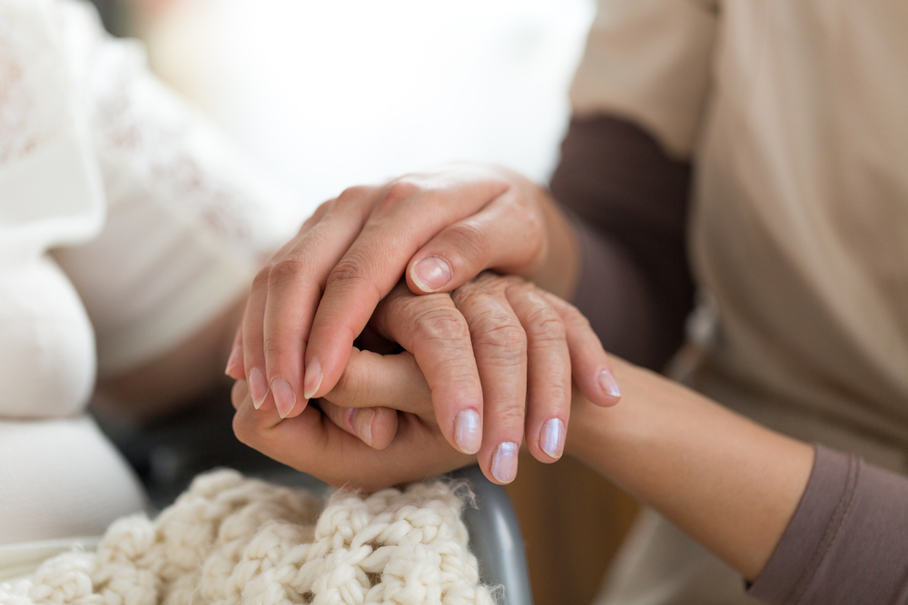 Technician holding the hand of a patient